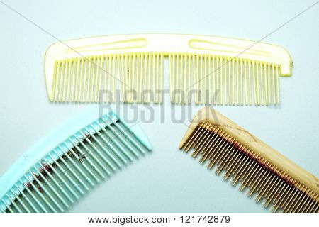 Old dirty and broken colorful comb with hair on gray background.