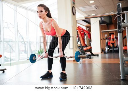 Full length of beautiful young sportswoman doing exercises with barbell in gym