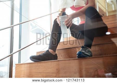 Closeup of attractive sportswoman sitting and drinking water