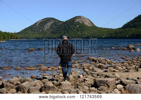 New England autumn and man walking or hiking through Acadia National Park in Maine