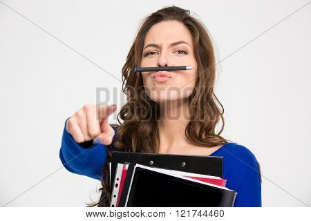 Funny young woman with folders simitating moustache with pen and pointing on camera over white background