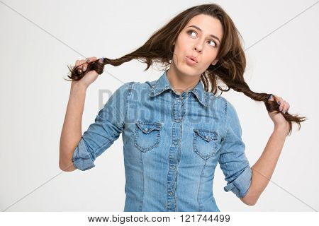 Playful pensive cute young woman grimacing and holding her hair as two braids over white background