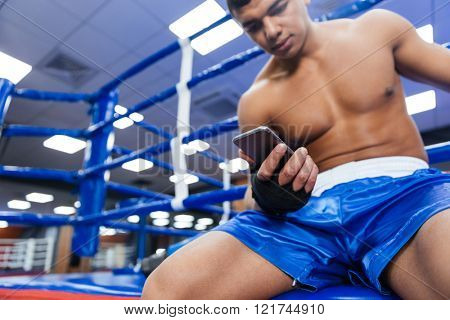 Handsome male boxer using smartphone in gym