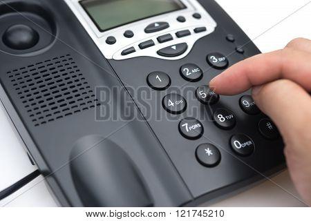 man dialing a black telephone close up