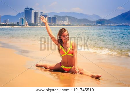 Blonde Slim Girl In Bikini Makes Split On Wet Sand Smiles At Sea