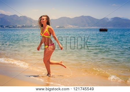 Blonde Slim Girl In Bikini Runs Out Of Sea To Beach Laughs