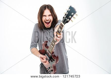 Excited popular young male singer with long hair shouting and playing electric guitar over white background