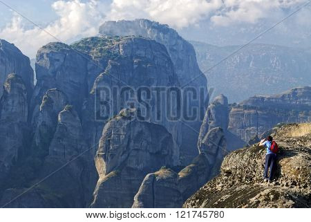 A tourist standing at the edge of the cliff to take photo of the Meteora