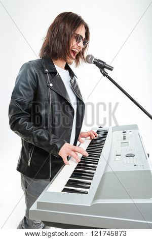 Profile of charismatic young man with long hair playing on synthesizer and singing in microphone over white background