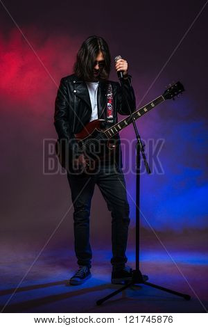 Handsome young male singer with long hair singing in microphone and playing guitar over colorful smoky background