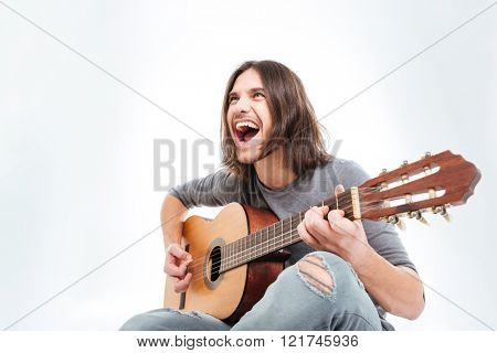 Happy young man with long hair playing guitar and singing over white background
