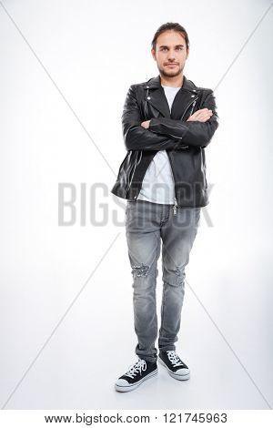 Confident attractive young man in leather jacket and jeans standing with arms crossed over white background