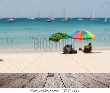 Wood table top on blurred blue sea and white sand beach with some people - Can used for display or montage your products