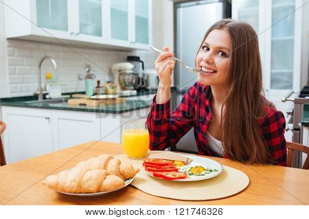 Cute smiling young woman eating fried eggs and drinking juice for breakfast on the kitchen at home