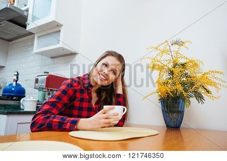 Cheerful pretty young woman drinking coffee on the kitchen at home