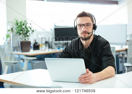 Businessman sitting at the desk with laptop computer in call center
