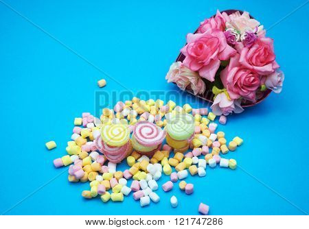 Colorful spiral jelly and colorful marshmallows on blue background, in red heart shaped box. Focus on jelly.
