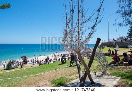 COTTESLOE,WA,AUSTRALIA-MARCH 12,2016: Metal thready sculpture on the Cottesloe Beach foreshore overlooking tourists enjoying the interactive arts festival Sculptures By The Sea in Cottesloe, Western Australia.