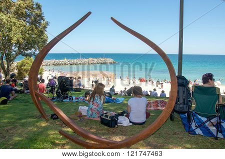 COTTESLOE,WA,AUSTRALIA-MARCH 12,2016: View through modern metal sculpture and tourists enjoying the interactive public arts festival Sculptures By The Sea at Cottesloe Beach in Cottesloe, Western Australia.