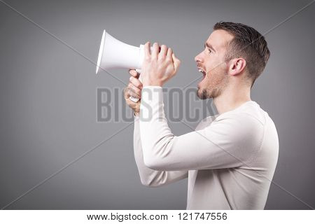 Casual man screaming with a megaphone on grey background