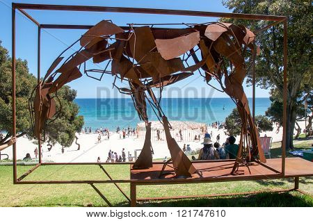 COTTESLOE,WA,AUSTRALIA-MARCH 12,2016: Metal horse sculpture overlooking Cottesloe Beach with tourists at the