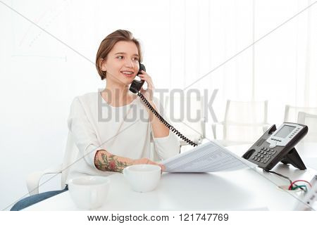 Smiling beautiful young woman sitting in office and talking on telephone