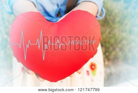 Women presenting red heart with pulse or heart beat and text healthy on for health background with copy space