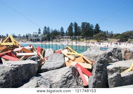 COTTESLOE,WA,AUSTRALIA-MARCH 12,2016: Wooden sculpture on the rock breakwater with tourists at the