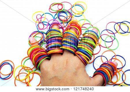 Colorful rubber/elastic bands in fingers, isolated on white.