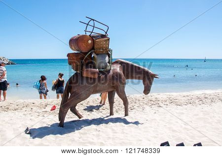 COTTESLOE,WA,AUSTRALIA-MARCH 12,2016:  Horse with a large load sculpture with tourists at the interactive free public arts festival