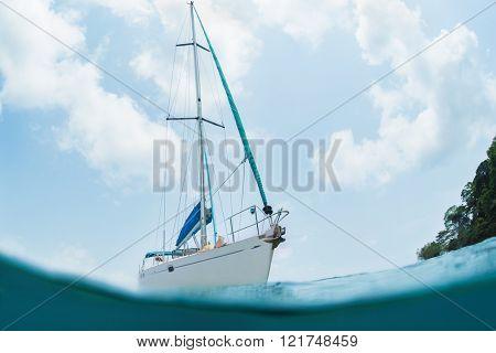 White sail boat in the sea. Underwater splited shoot