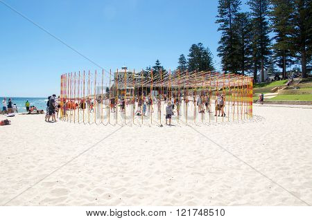 COTTESLOE,WA,AUSTRALIA-MARCH 12,2016:  Circular pole and ribbon sculpture with people at the interactive arts festival