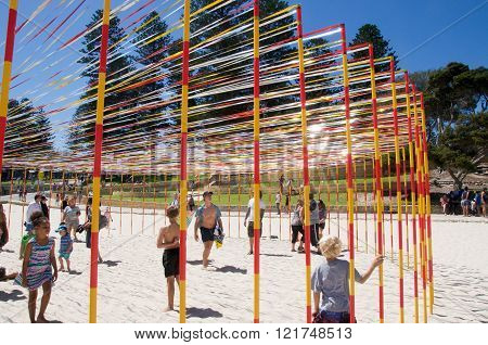 COTTESLOE,WA,AUSTRALIA-MARCH 12,2016:  Families with the pole and ribbon sculpture at the interactive free public arts festival