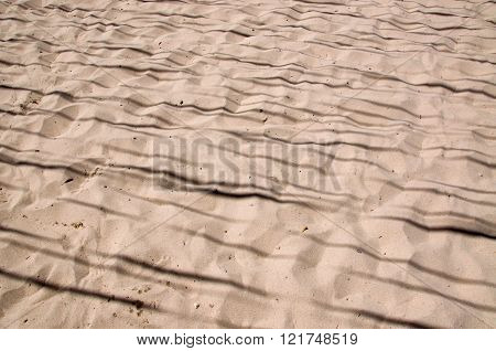 Background of beach sand with shadow lines and surface texture.