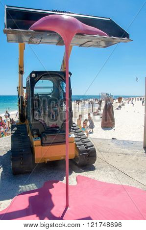COTTESLOE,WA,AUSTRALIA-MARCH 12,2016:  Backhoe sculpture dripping with pink and people at the interactive free public arts festival