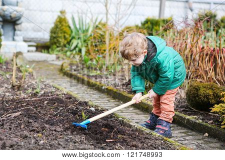 Little boy in spring lanting and gardening
