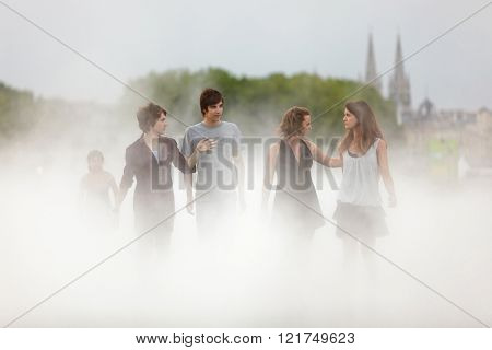 BORDEAUX, FRANCE, JUNE 26, 2010 : A group of young friendly people is walking in the fog made by the water mirror at the Bourse place in Bordeaux, france