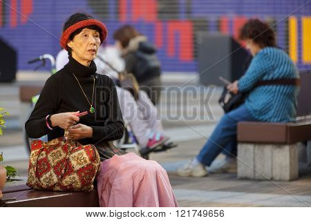 OSAKA, JAPAN, NOVEMBER 13, 2011 : A well dressed classy lady is sitting on a bench in a city square of Osaka, Japan