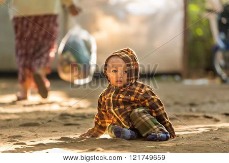 BAGAN, MYANMAR, JANUARY 24, 2015: A Burmese little child is sitting in the street of the old Bagan village in Myanmar (Burma)