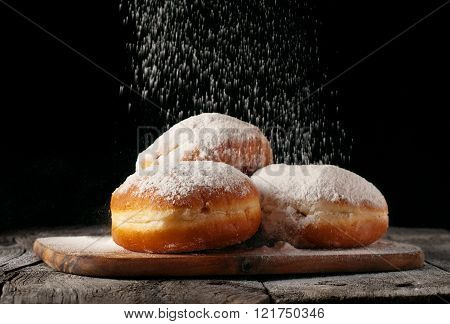 Donuts sprinkled with powdered sugar on wooden table on black background closeup. Food background