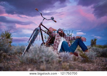 bearded man with bike in desert shouting