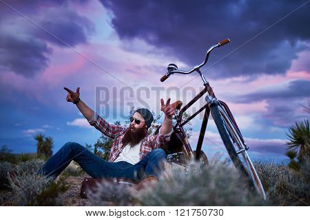 bearded traveler with suitcase and bike in the desert shouting with arms up