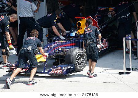 KUALA LUMPUR - APRIL 2: Red Bull team mechanics push Sebastian Vettel's car back into the garage on practice day at the 2010 Petronas Malaysia F1 Grand-Prix on April 2, 2010 in Sepang, Malaysia.