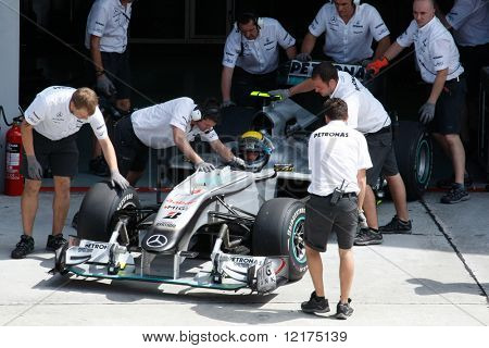 KUALA LUMPUR - APRIL 2: Mercedes' mechanics push Nico Rosberg's car back into the garage after his practice run at the 2010 Petronas Malaysia F1 Grand-Prix on April 2, 2010 in Sepang, Malaysia.