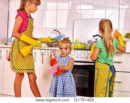 Children little girl wash kitchen at kitchen. Kitchen cleaners.