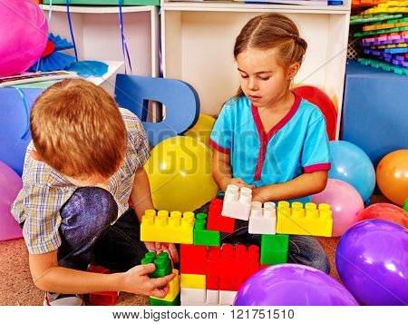 Couple children boy and girl game blocks on floor in kindergarten. Kindergarten decorated with balloons.