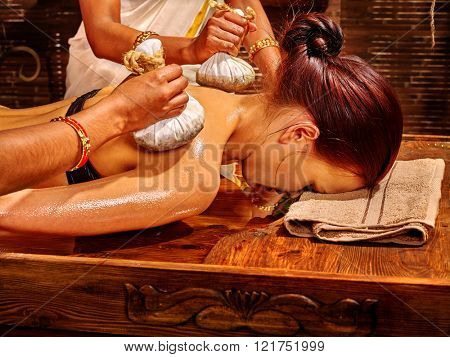 Woman having Ayurveda massage with herbal ball. Massage the basis of health.