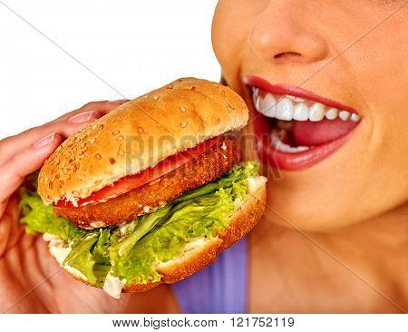Girl eats big hamburger fast food. Fastfood concept.
