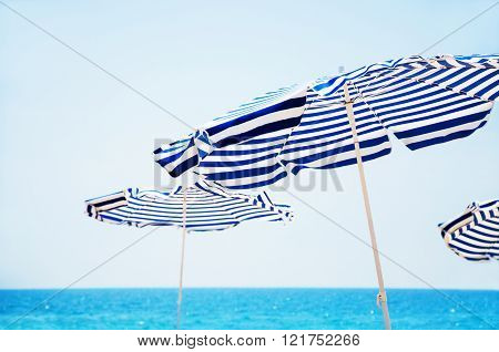 Beach Umbrellas, Blue Sea And Sky In Background.