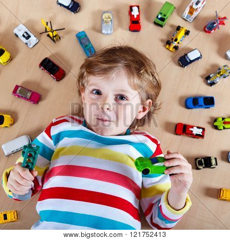 Little blond child playing with lots of toy cars indoor